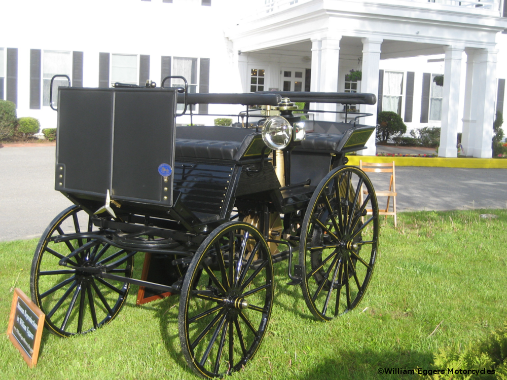 Antique car in front of white mansion